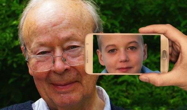 A old man having his photo taken but an image of his younger self appears on the screen instead.