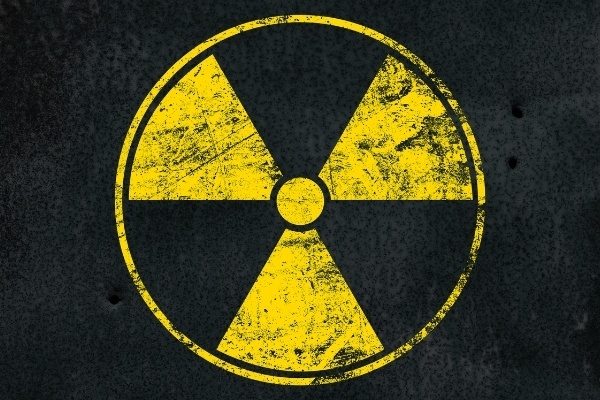 A yellow radioactive symbol on a black background.