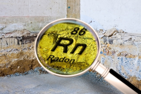 A basement foundation with a magnifying glass superimposed over the image. In the middle of the magnifying glass is the symbol for radon.
